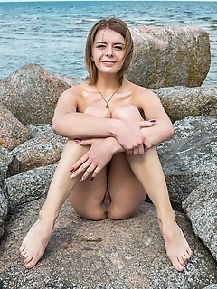 Yelena yelena shows off her big tits as she strips by the rocky beach.
