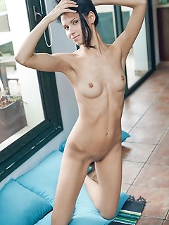 Alecto alecto bares her perky tits and petite body in front of the camera.