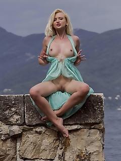 Nika n nika n displays her petite body as she poses by the beach.