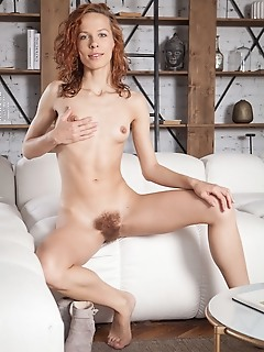 Dennie dennie spreads her legs wide open as she bares her unshaven pussy on the couch.