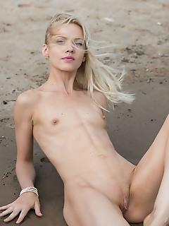 Camelia new model camelia sensually strips at the beach as she bares her petite body.